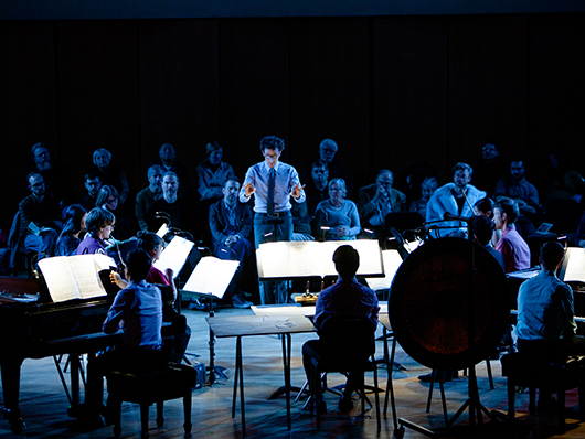 Conductor in front of Contemporary Music Ensemble musicians on a dark stage