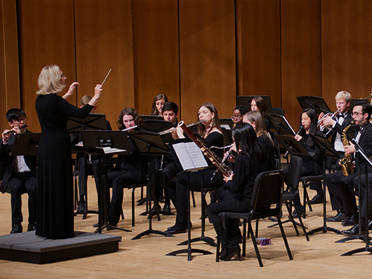 Conductor in front of Symphonic Wind Ensemble performing on a well lit stage