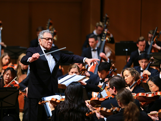 Conductor Victor Yampolsky in front of Northwestern University Symphony Orchestra performing on a well lit stage