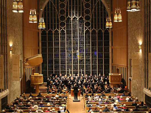Alice Millar Chapel with audience members watching a conductor and musicians perform on stage