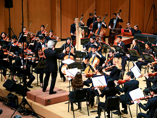 Conductor in front of Northwestern University Chamber Orchestra performing on well lit stage