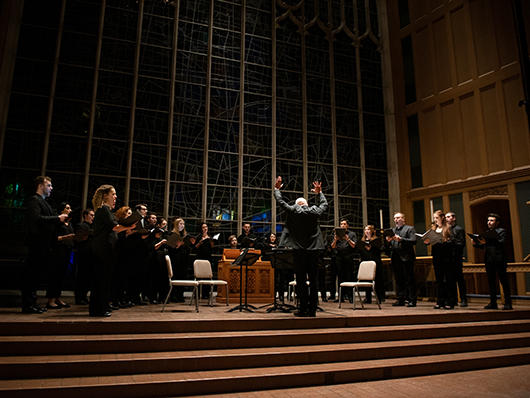 Conductor in front of musicians performing on dimly lit stage in St. Luke's Episcopal Church