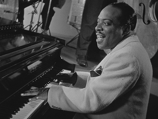 Black and white photo of Count Basie playing the piano