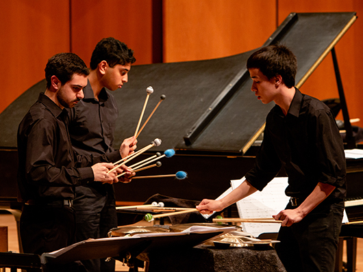 Percussionists performing on a well lit stage