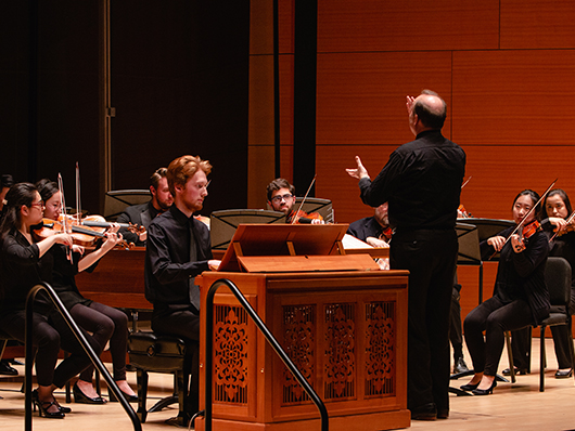 Conductor in front of Baroque Music Ensemble performers on well lit stage