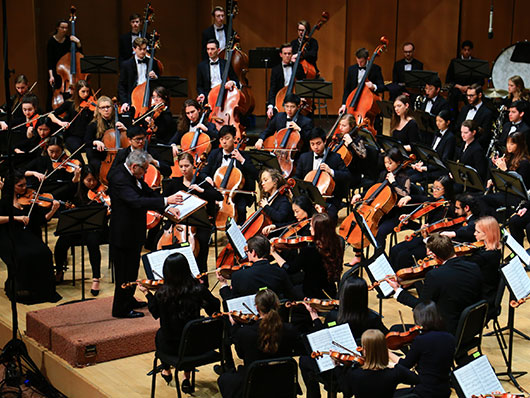 Conductor Victor Yampolsky in front of Northwestern University Symphony Orchestra performing on well lit stage