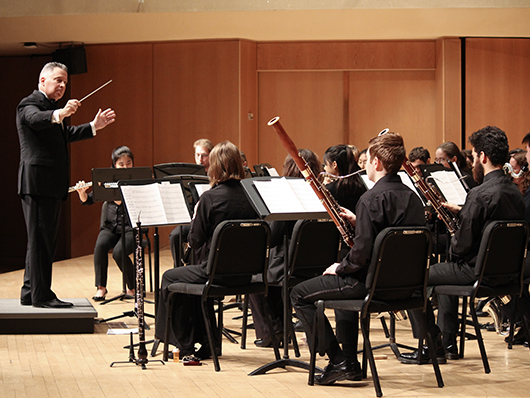 Daniel J. Farris in front of Concert Band performing on well lit stage