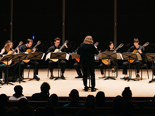 Guitar ensemble performing on well lit stage