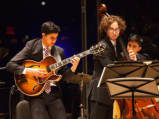 Jazz performers play on well lit stage
