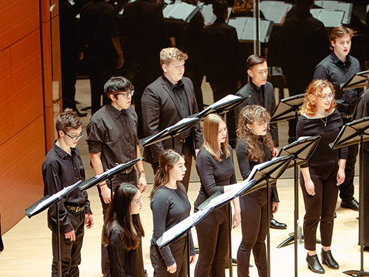 university singers on stage with stands